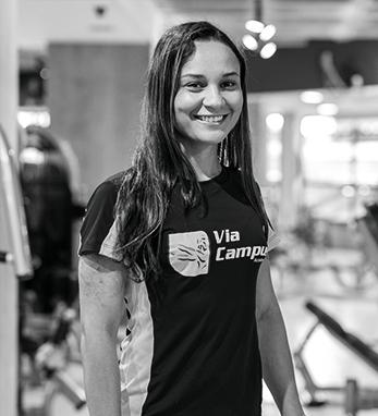 Uma mulher chamada Wanessa sorrindo com o uniforme da Via Campus.