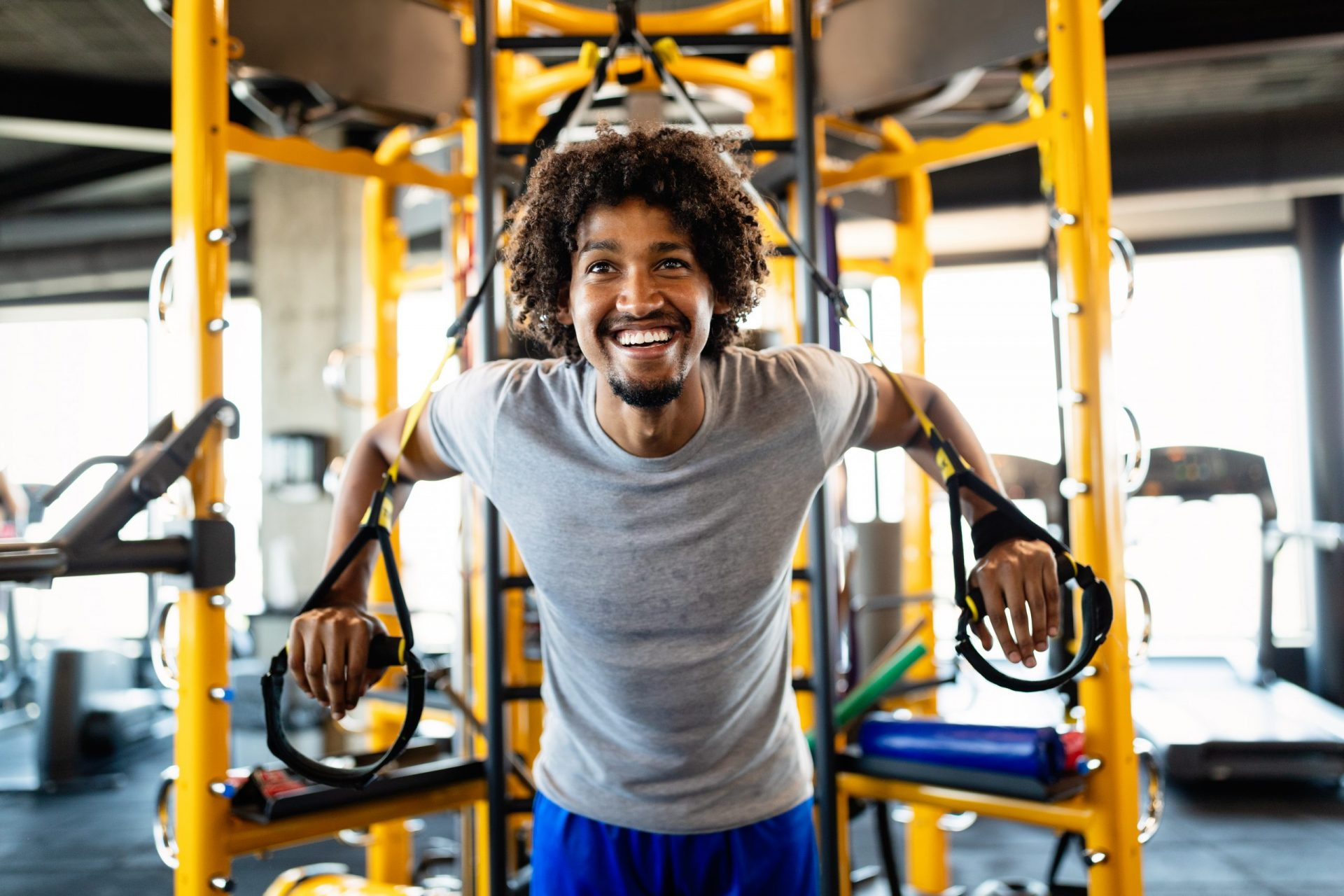 Fit handsome man having fitness TRX training at gym