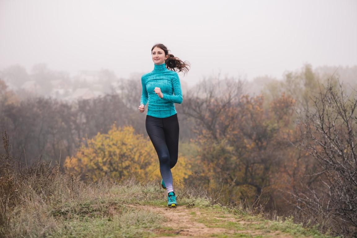 Vista frontal do ajuste saudável atrativo da mulher desportiva nova que movimenta-se para a câmera na floresta enevoada no outono.