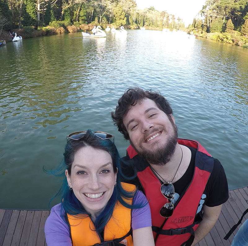 casal em primeiro plano com colete salva vidas de costas para o lago negro em gramado. pedalinhos em cines ao fundo.