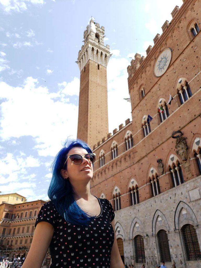 mulher de cabelo azul em frente ao palacio publico e torre mangia em siena
