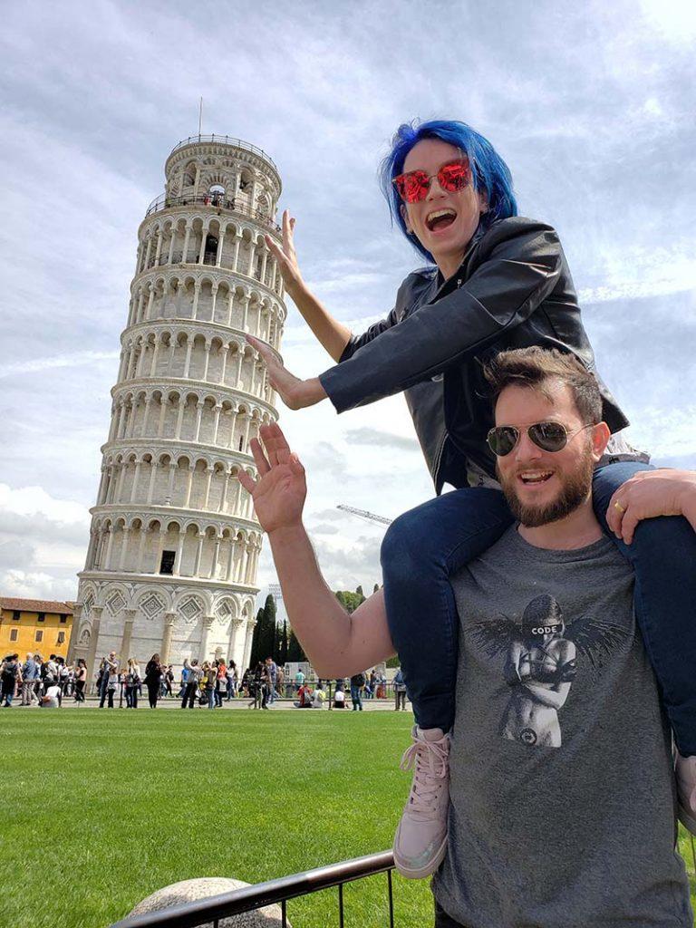 casal segurando a torre de pisa