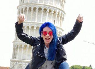 mulher de cabelo azul fazendo pose de luta em frente a torre inclinada