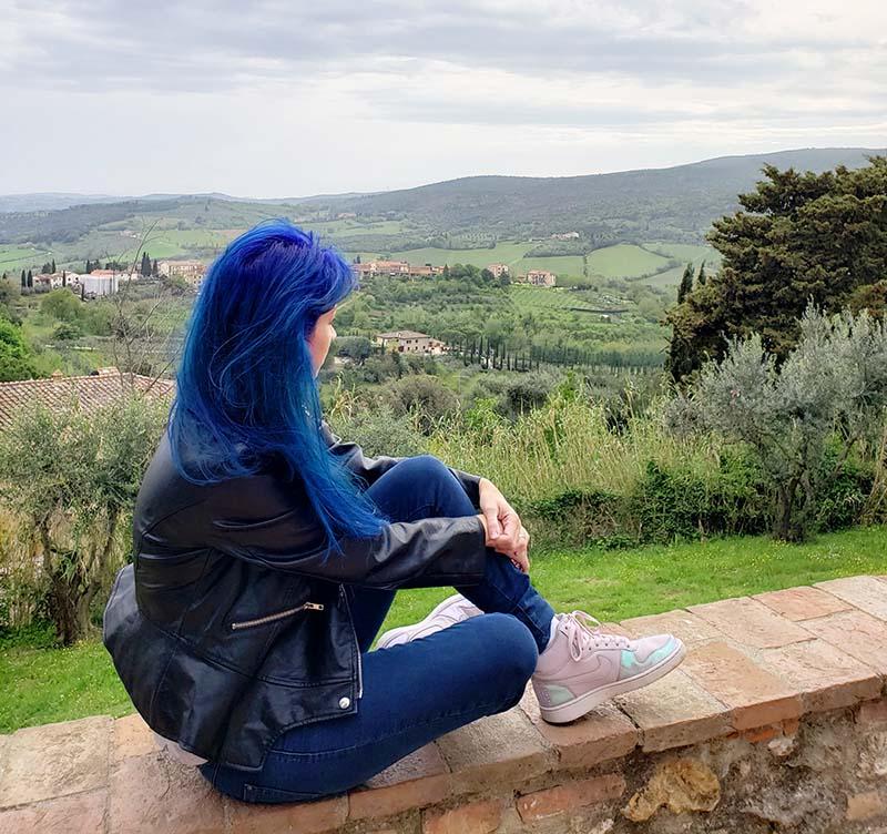 mulher de cabelo azul olhando para vinhedos em san gimignano toscana