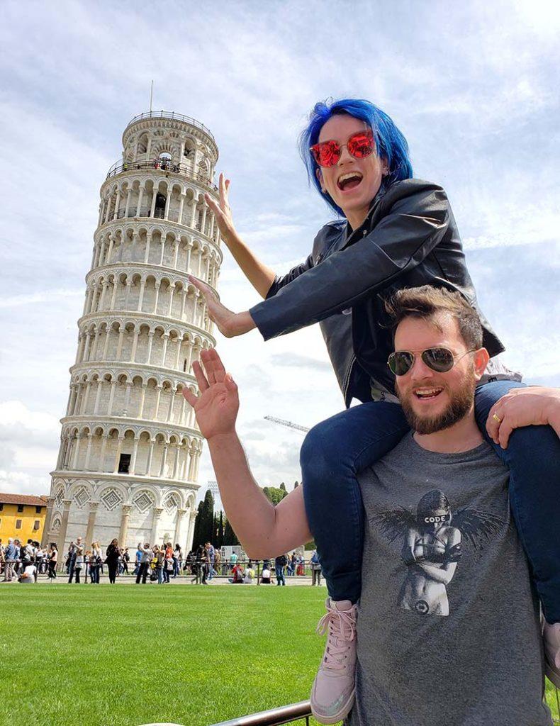 mulher nos ombros de homem segurando a torre de pisa na italia