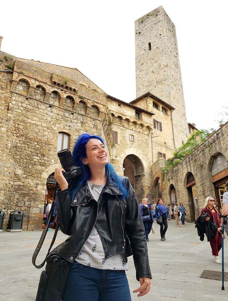mulher segurando camera com uma mao ao lado de torre em san gimignano na italia