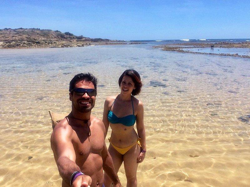 Casal em frente a uma piscininha rasa no mar de pernambuco