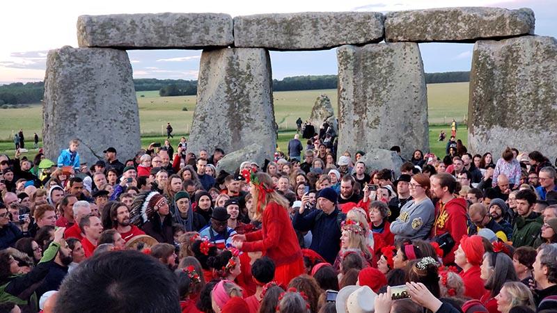 grupo cantando no centro de stonehenge