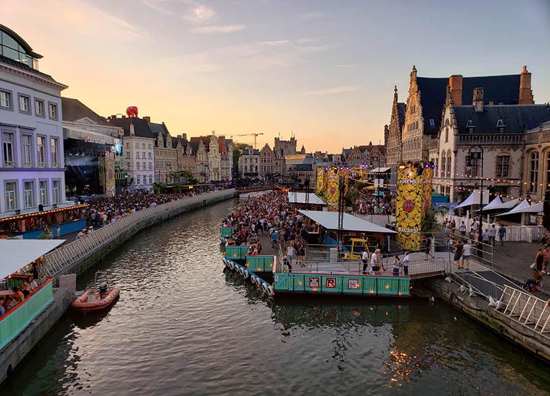 Canal e deque com palco no Gentse Feesten no fim da tarde