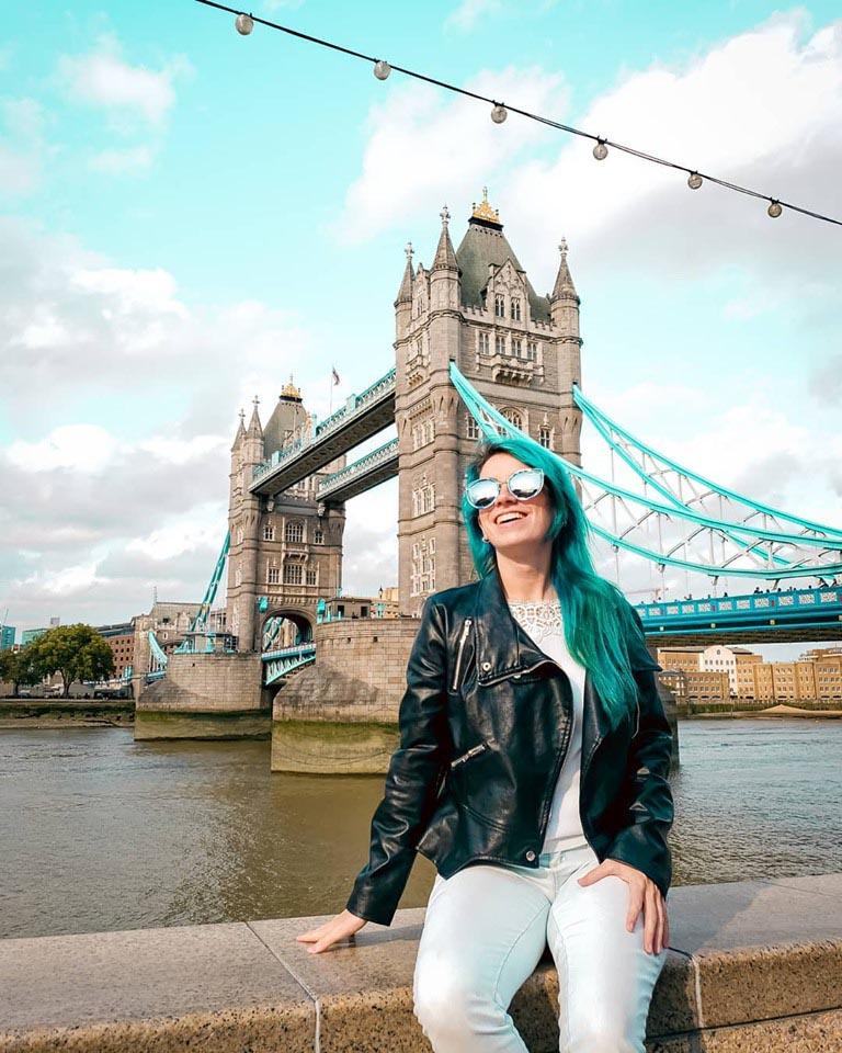 mulher de cabelo azul sentada na mureta feliz com tower bridge ao fundo num ceu azul