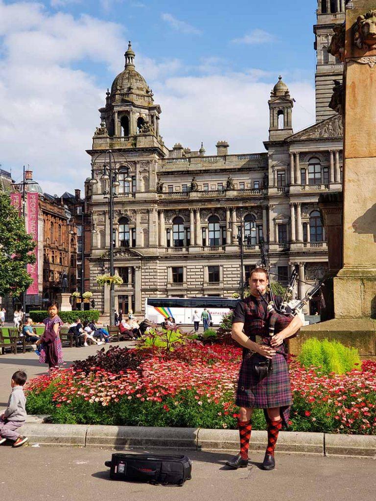 Escocês tocando gaita de fole vestido com kilt na George Square em Glasgow