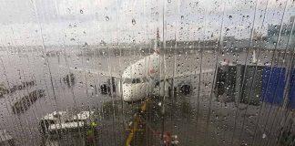 aviao parado em aeroporto na chuva