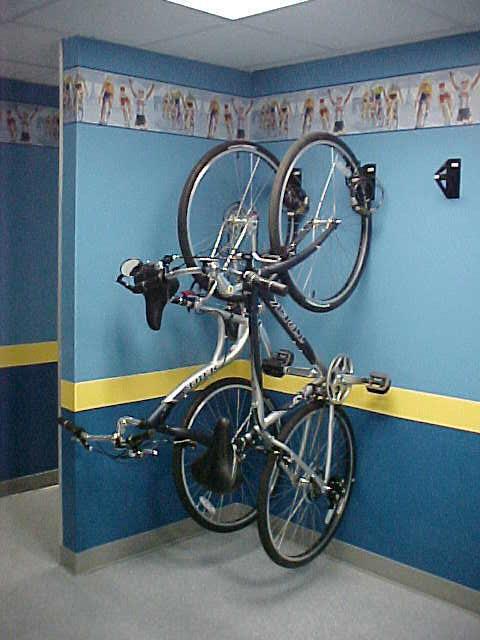 guardar a bicicleta no apartamento: parede escura e proteção para as rodas