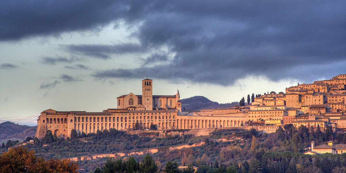 Panorama de Assisi, com a Basílica de São Francisco. Di Roberto Ferrari from Campogalliano (Modena), Italy - Assisi, CC BY-SA 2.0, https://commons.wikimedia.org/w/index.php?curid=5006520