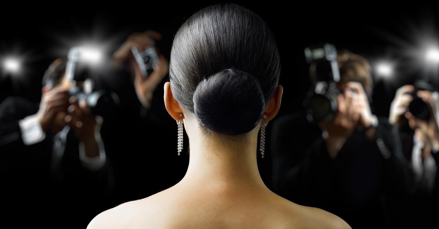 Foto mostrando o poder dos influenciadores digitais. Uma mulher sendo fotografada por diversos paparazzis