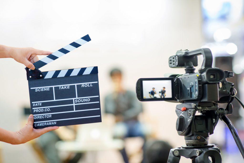 Imagem de uma câmera, claquete e um homem gravando, para mostrar como gravar vídeo mesmo sem grana