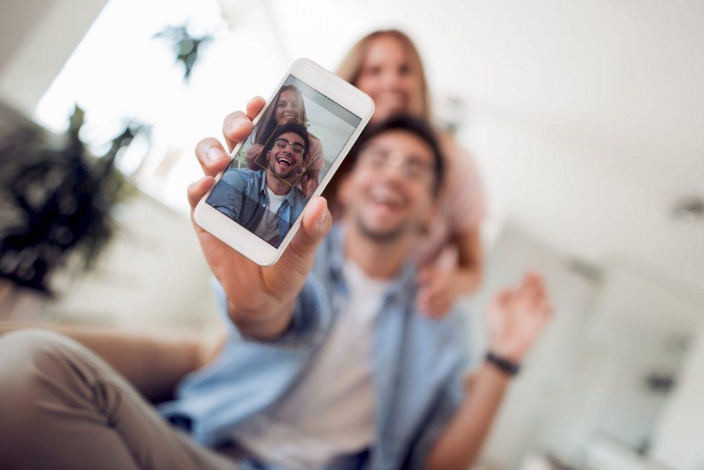 Foto de um casal tirando selfie na medida dos stories do Instagram