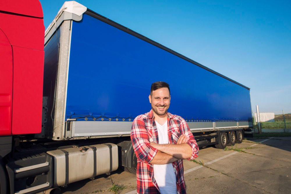 portrait of middle aged trucker with arms crossed standing by truck trailer ready for driving