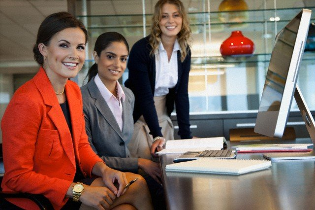 Three women in office working with laptop