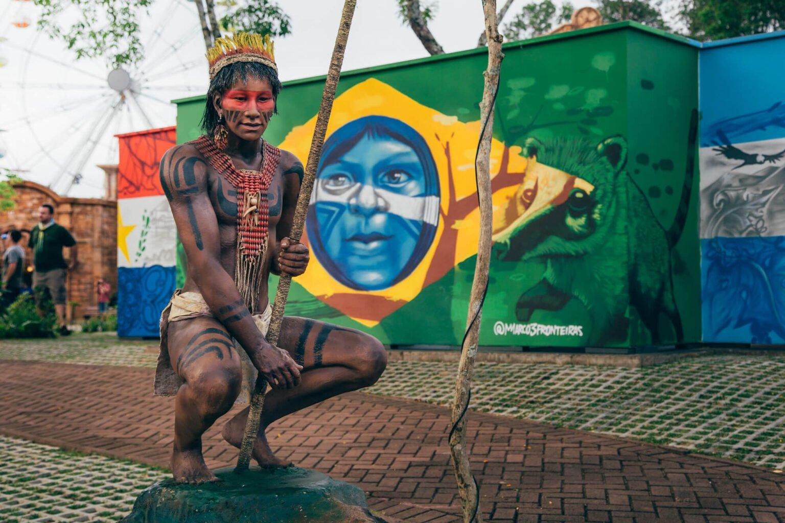 Estátua de um índio com o labirinto cultural ao fundo