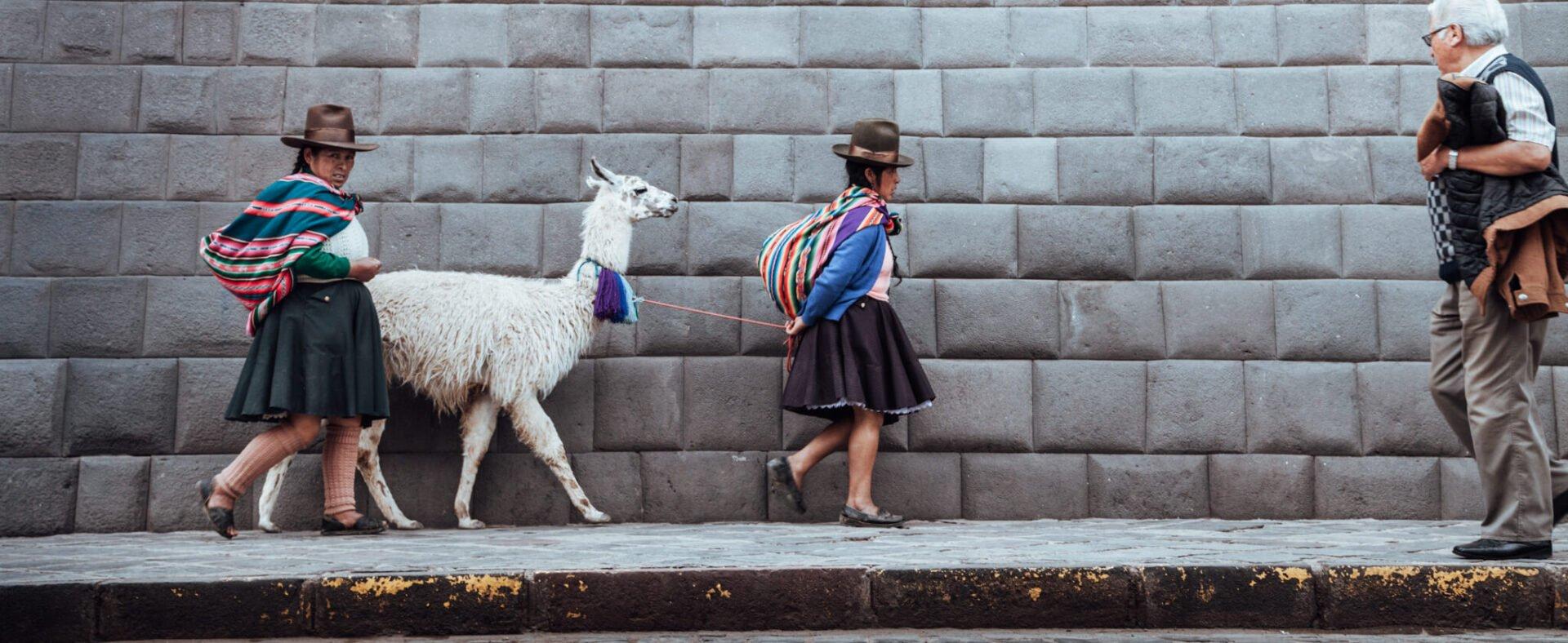 Cholas andando com uma lhama no centro de Cusco