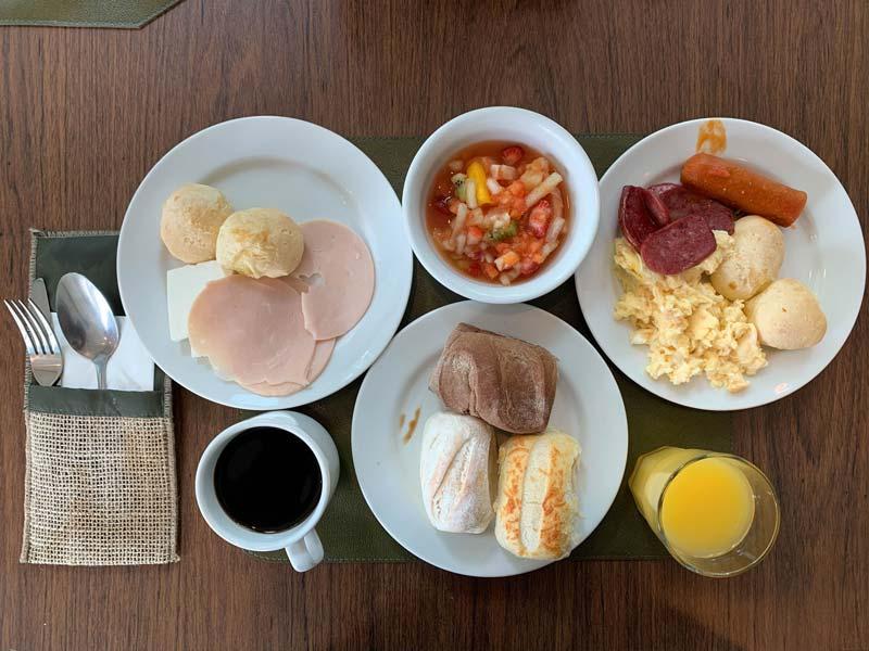 Diversos pães, suco, café, salada de frutas no café da manhã