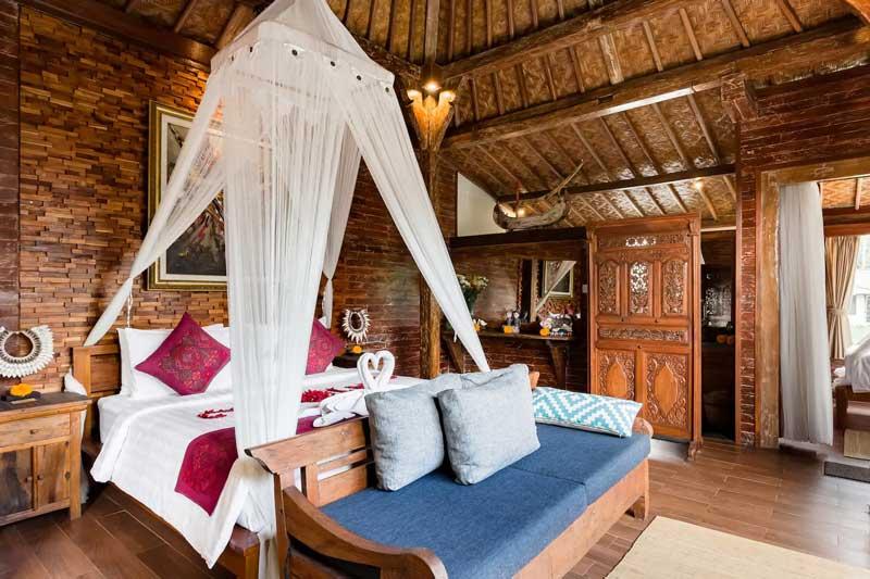 Grande cama com mosquiteiro em quarto de madeira