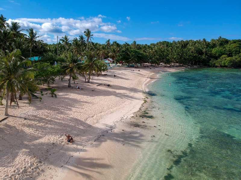 Vista aérea de praia paradisíaca com água transparente, nas Filipinas.