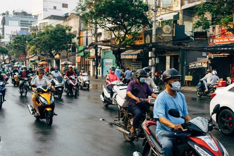 Trânsito intenso de Scooters e pessoas com máscara no sudeste asiático.