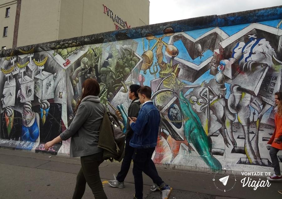 Galera passando pelo grafite dos capitalistas quadrados