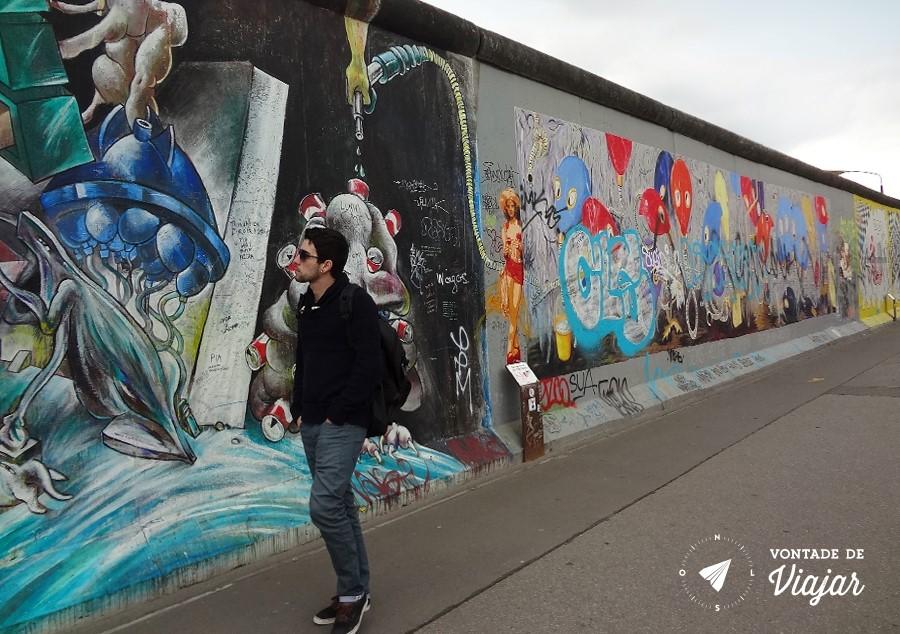 East Side Gallery - Rapaz passando pelo Muro de Berlim graffiti Pneumohumanoiden